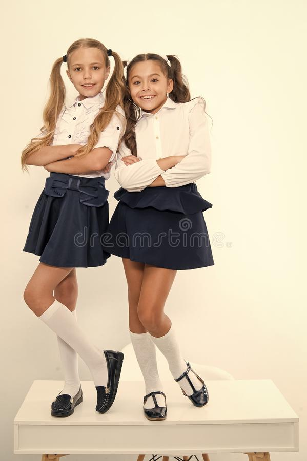 Happy girls smile in school uniform. Back to school. Pretty dresses little curls, thank heaven for little girls.  royalty free stock photo