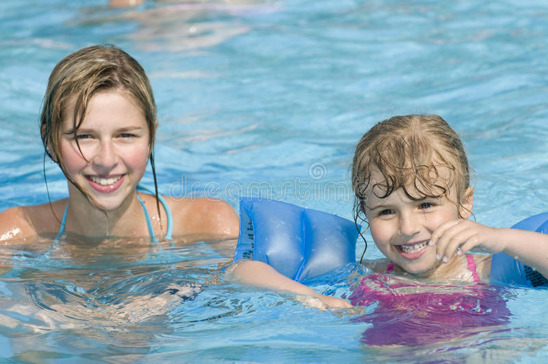 Happy girls on swimming pool royalty free stock photos