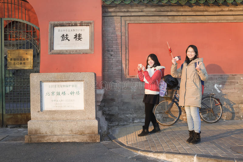 Happy girls. Two girls are sightseeing in sunset and taking picture at root of famous Gulou Building very happily, China royalty free stock image