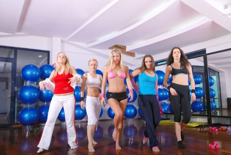 Happy Girls Walking Ahead In Fitness Studio Stock Photo