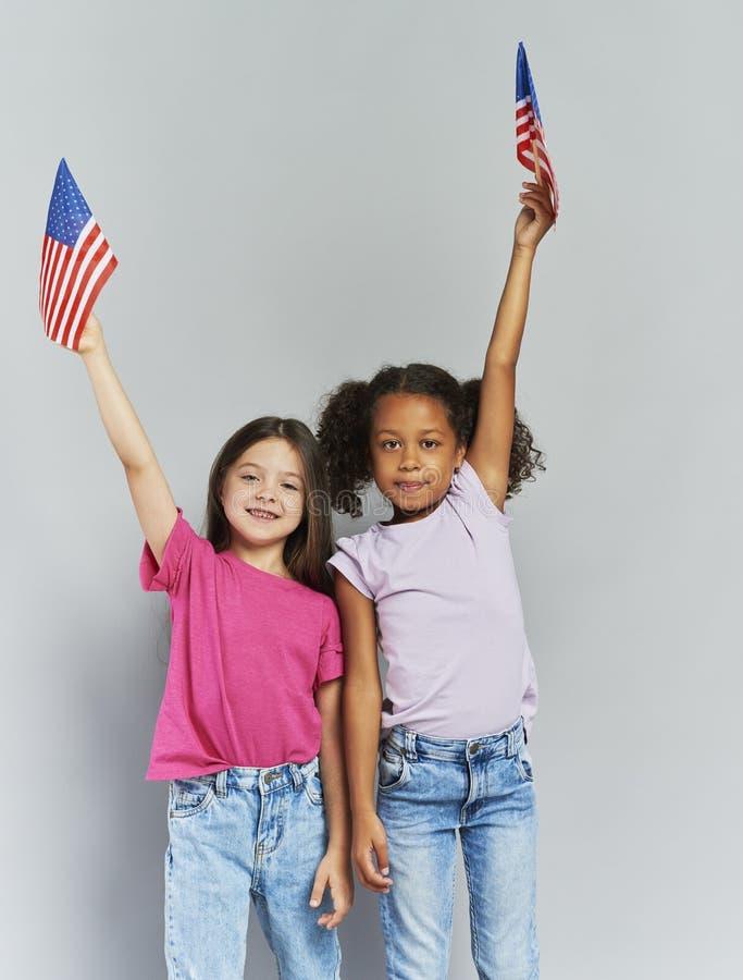 Girls waving American flags. Happy girls waving American flags stock images