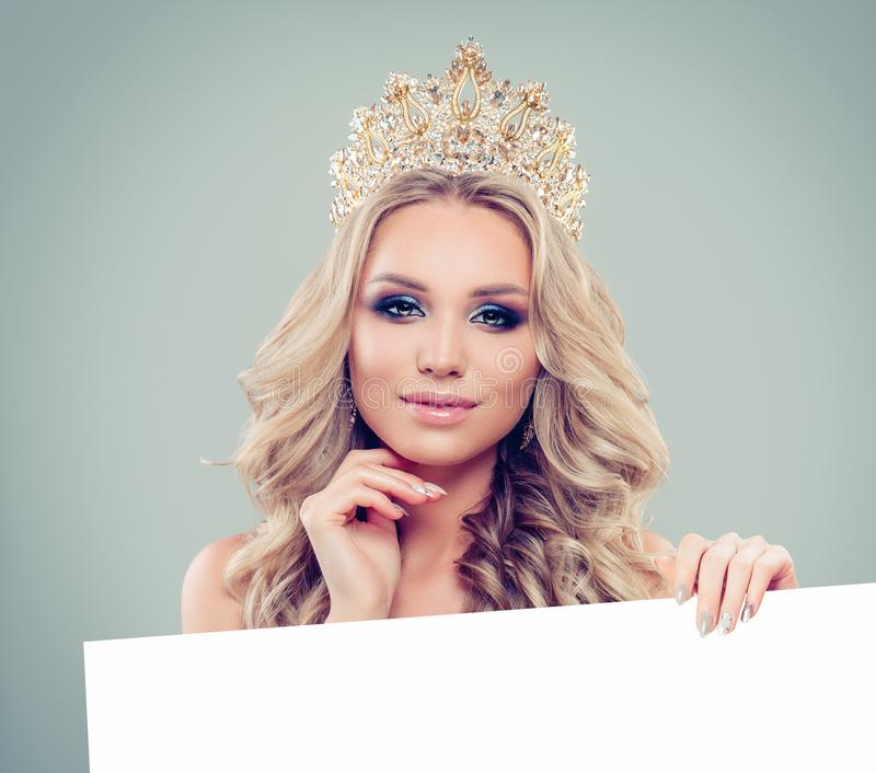 Happy glamorous woman in gold crown with white empty paper board background. Happy girl portrait stock photo