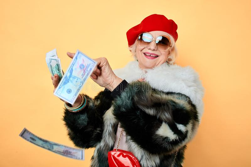 Happy glamour senior old lady throwing stack of dollar bills stock photo