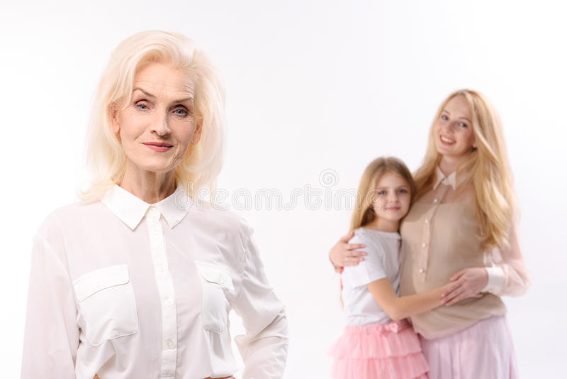 Happy glances of female persons. Curious old women is standing afore her daughter and granddaughter. They are hugging each other. Isolated. Portrait stock images