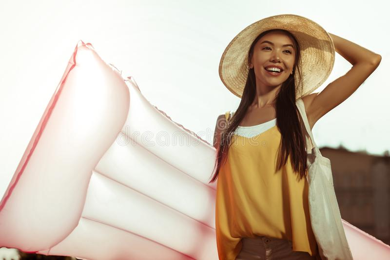 Happy glowing smiling woman holding inflatable air mattress for swimming royalty free stock images