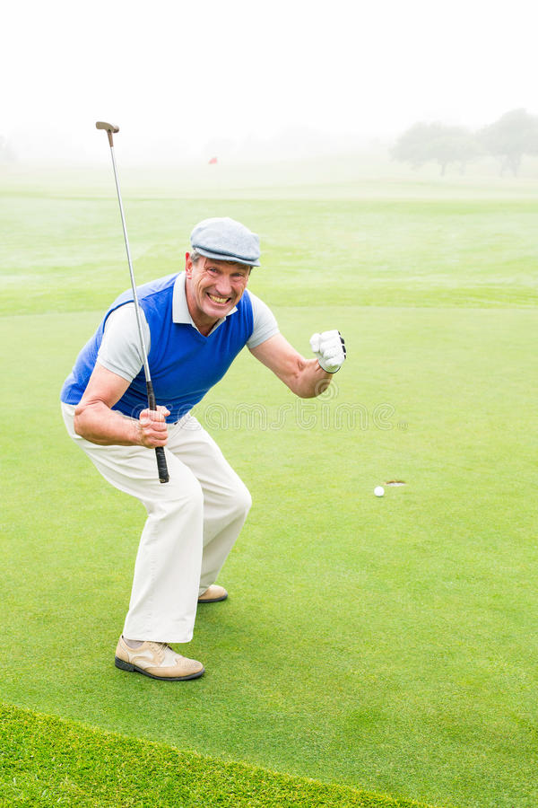 Happy golfer cheering on putting green royalty free stock photos