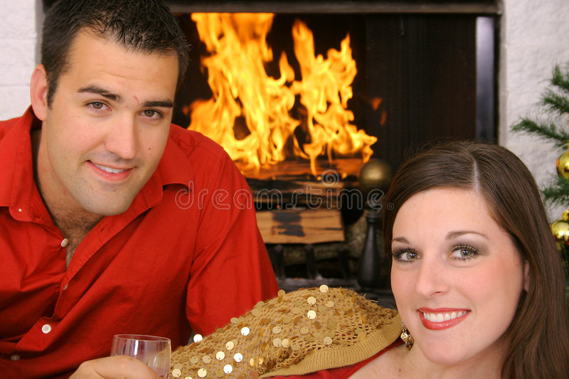 Happy gorgeous couple in front of fireplace stock photo