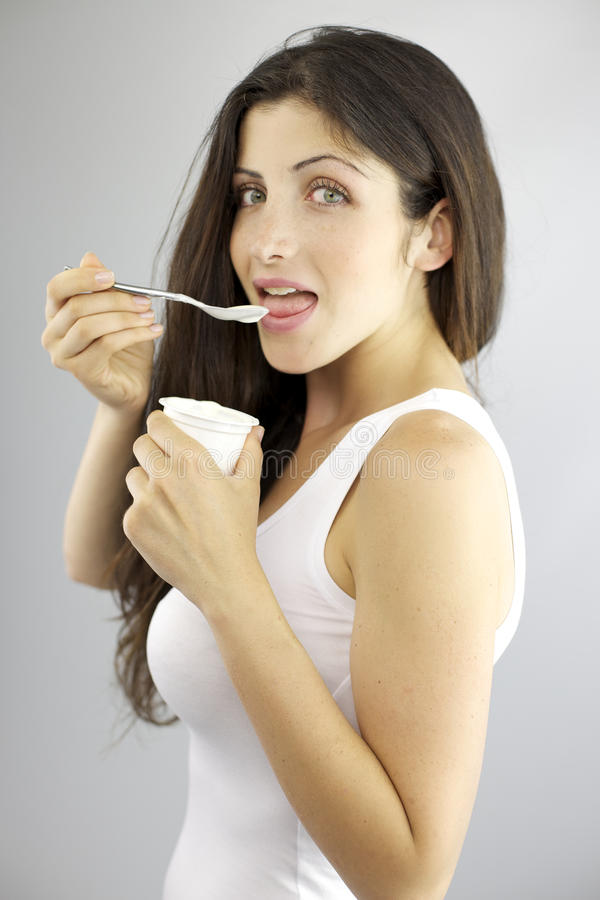 Happy gorgeous female model eating white yogurt being on a diet
