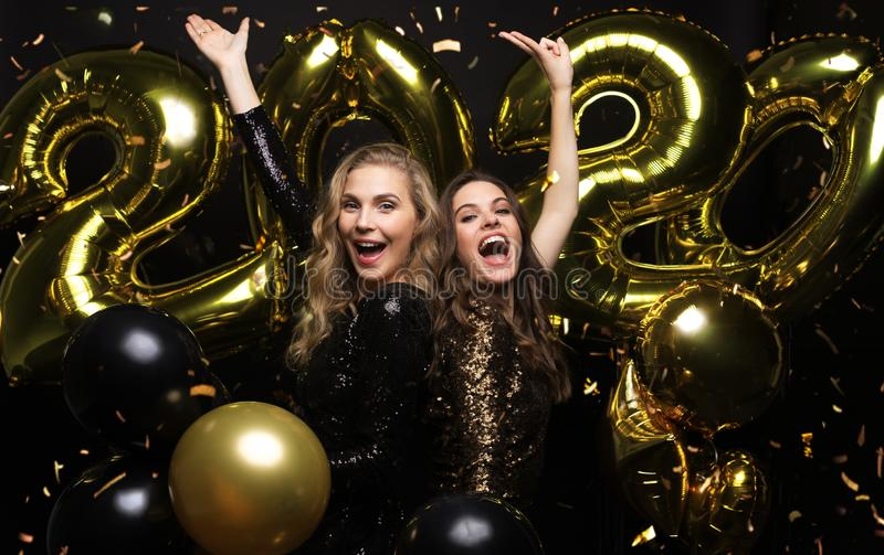 Happy gorgeous girls in stylish sexy party dresses holding gold 2020 balloons, having fun at New Year`s Eve Party royalty free stock photos