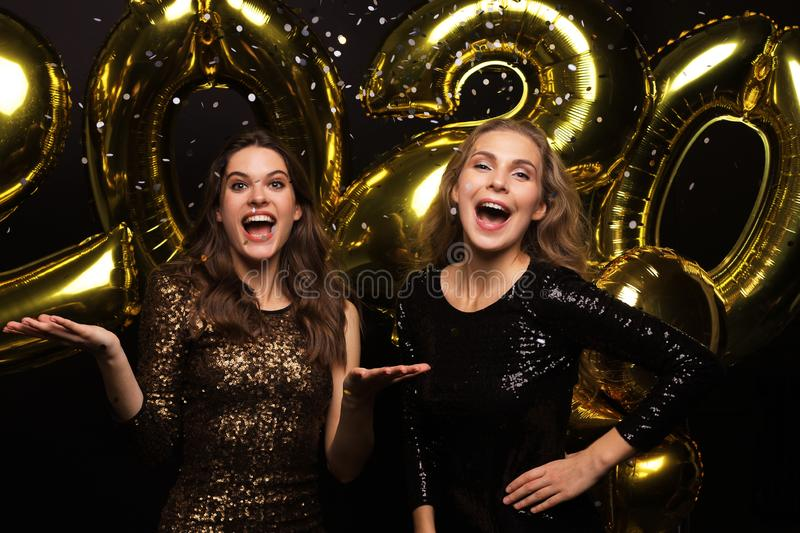 Happy gorgeous girls in stylish sexy party dresses holding gold 2020 balloons, having fun at New Year`s Eve Party.  stock image
