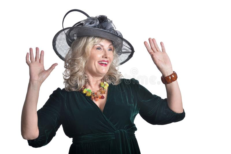 Happy gorgeous mature woman in hat posing isolated stock photography
