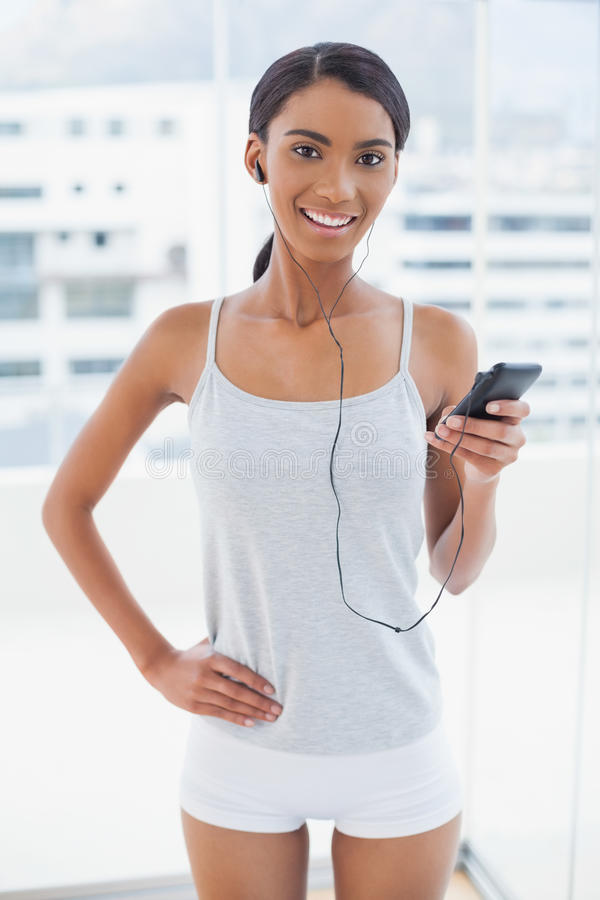 Happy gorgeous model in sportswear listening to music royalty free stock photos