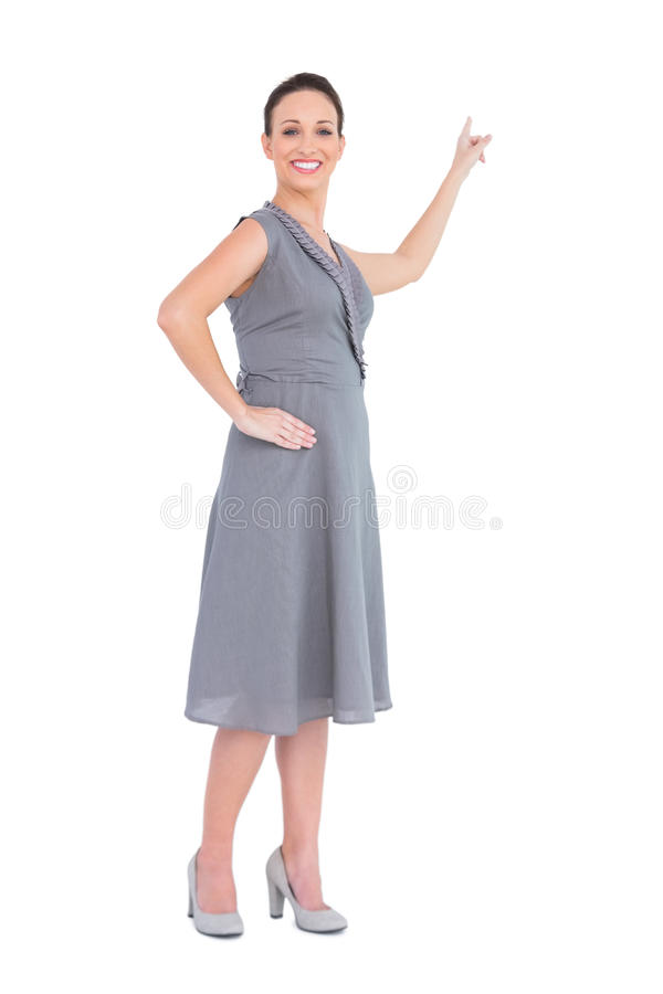 Happy gorgeous woman in classy dress pointing out direction royalty free stock image