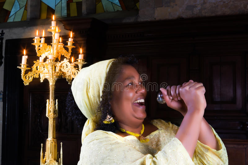 Happy gospel singer. With microphone singing during mass royalty free stock photography