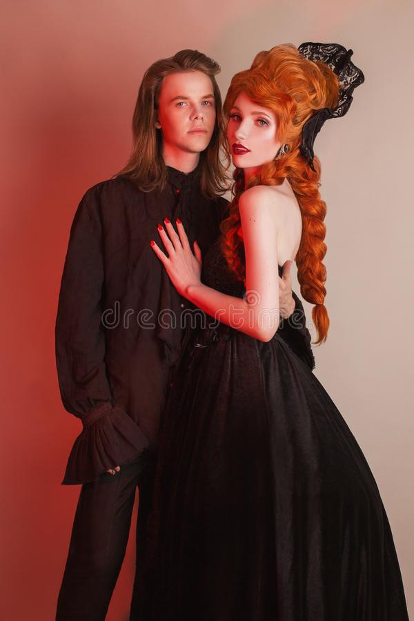 Happy gothic couple in halloween clothes. Vampire in renaissance dress. Gothic costume for halloween. Newlyweds couple on dark. stock image