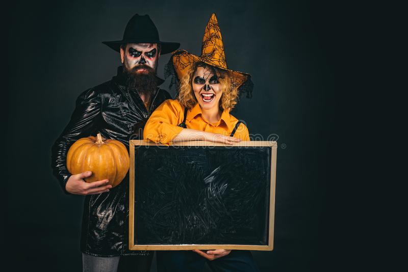 Happy gothic couple in Halloween costume. Jack-o-lanterns. Halloween poster or greeting card - people concept. stock images
