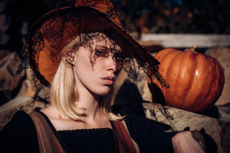 Happy gothic young woman in witch halloween costume. Halloween concept. Halloween Woman portrait. Witch posing with Pumpkin on wood background. Happy gothic stock photo