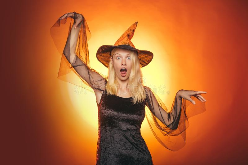 Happy gothic young woman in witch halloween costume with hat standing and smiling. Beautiful young woman in black witch. Costume with hat and broom standing stock photography