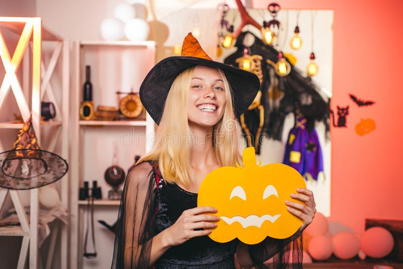 Happy gothic young woman in witch halloween costume with hat standing and smiling over white background. Vampire. Halloween Woman portrait. Attractive model stock image