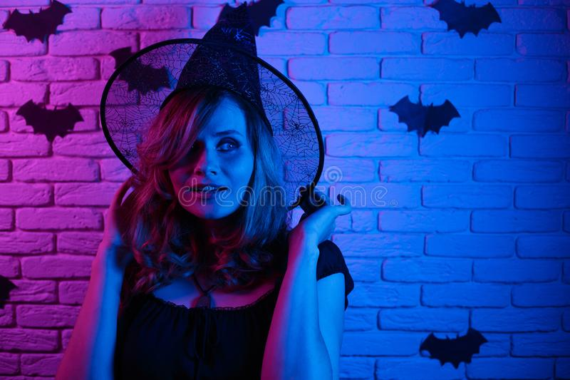 Happy gothic young woman in witch halloween costume partying in. A nightclub, image with free space for design. Halloween, celebration, party concept stock photography