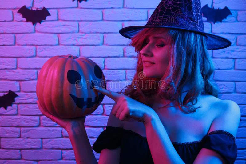 Happy gothic young woman in witch halloween costume with pumpkin. In hands partying in a nightclub. Halloween, celebration, party concept stock photography