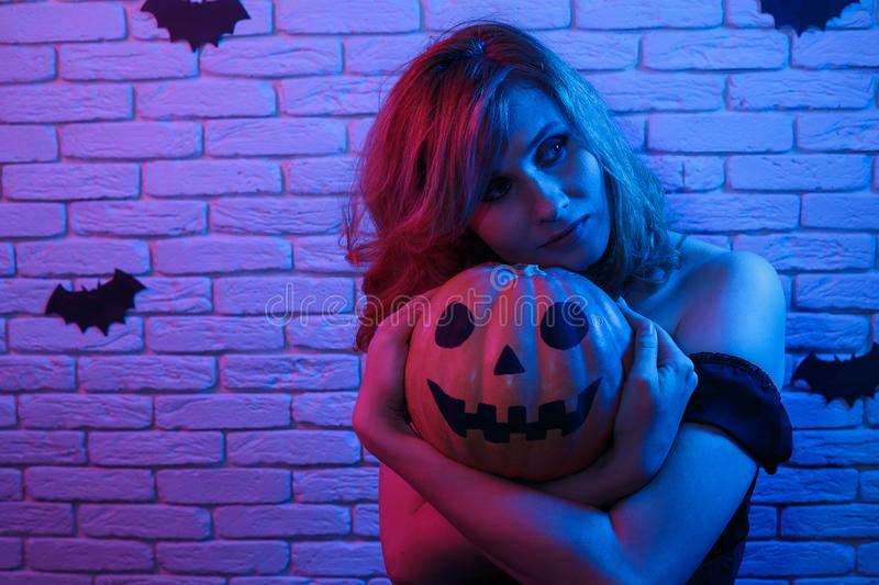 Happy gothic young woman in witch halloween costume with pumpkin. In hands partying in a nightclub. Halloween, celebration, party concept royalty free stock photo