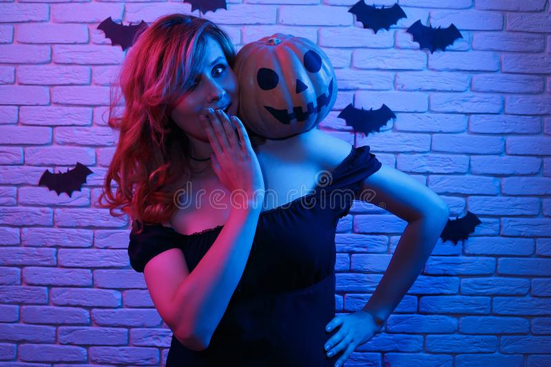 Happy gothic young woman in witch halloween costume with pumpkin. In hands partying in a nightclub. Halloween, celebration, party concept royalty free stock image