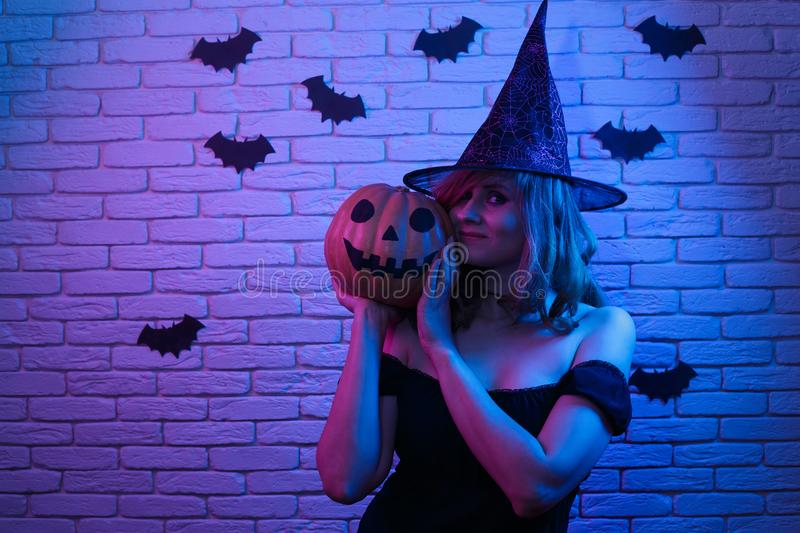 Happy gothic young woman in witch halloween costume and pumpkin. In hands partying in a nightclub. Halloween, celebration, party concept stock photos
