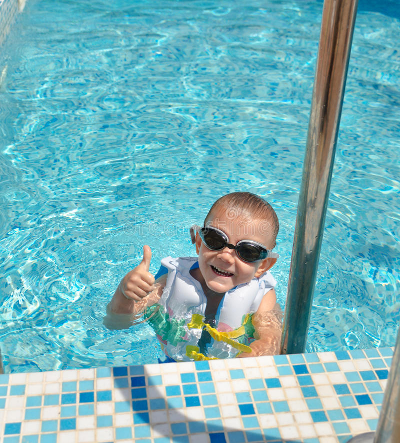 Happy goung boy swimming pool giving thumbs up. Young boy in a swimming pool wearing goggles and a flotation jacket giving a thumbs up of approval as he enjoys a royalty free stock images