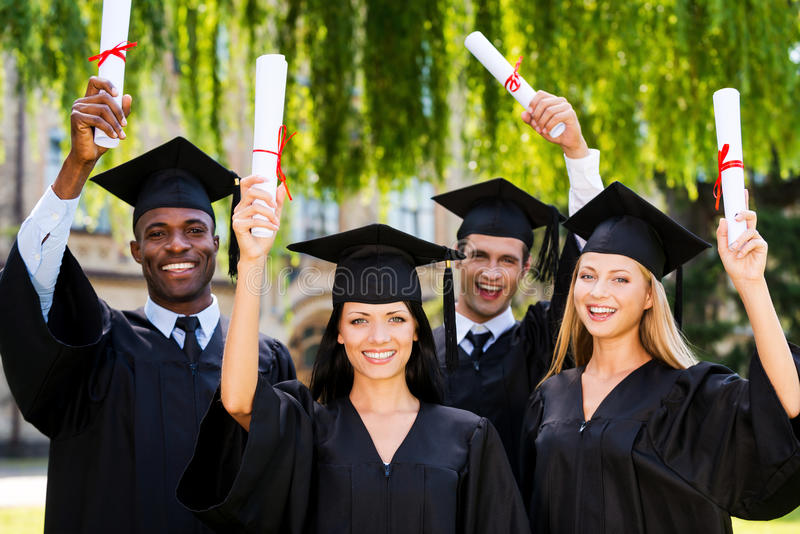 Happy graduates. Four college graduates showing their diplomas and smiling while standing close to each other and stock photography