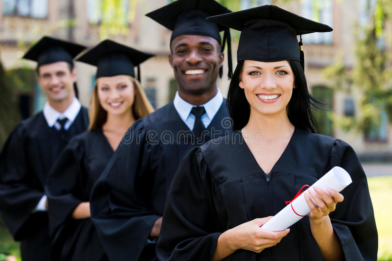 Happy graduates. Four college graduates standing in a row and smiling royalty free stock photos