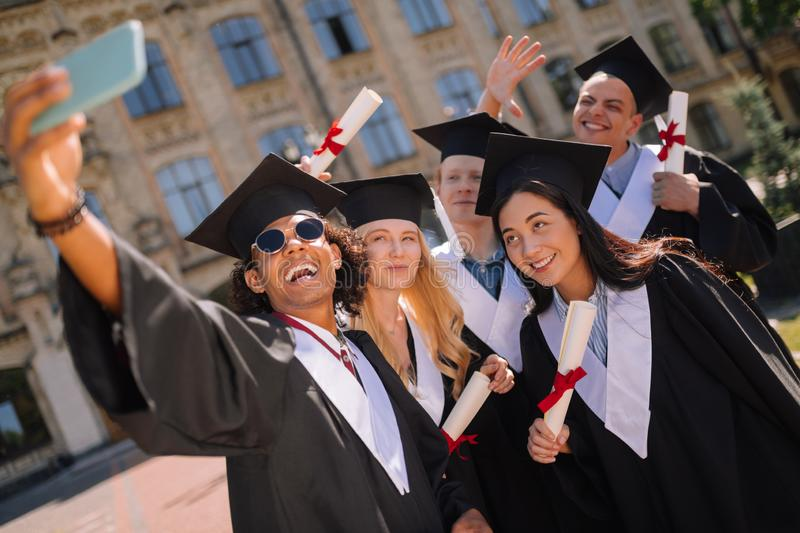 Happy graduates taking a selfie together near university. royalty free stock photography