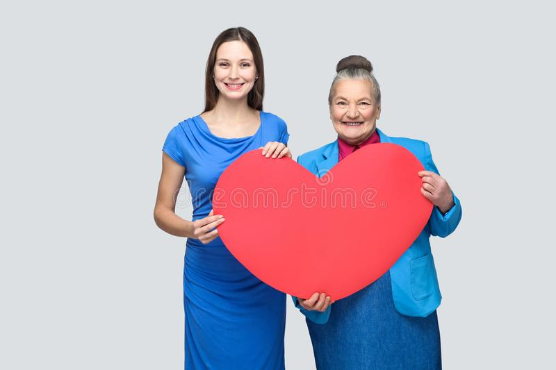 Big love in family. Happy granddaughter and grandmother standing, holding big heart shape, looking at camera with toothy smile. Big love in family. Relations in stock photo