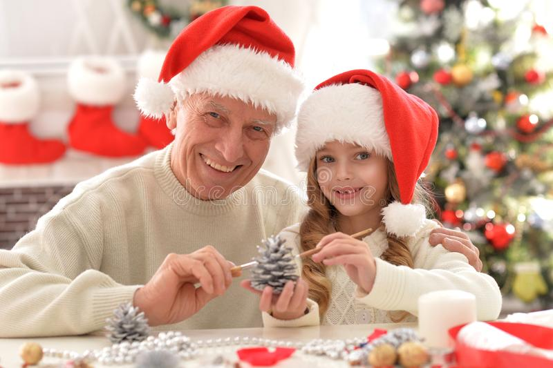 Happy grandfather and child in Santa hats preparing for Christmas, painting pine cone decoration stock image