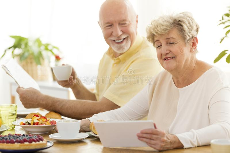 Happy grandfather drinking tea while grandmother using tablet during breakfast stock image