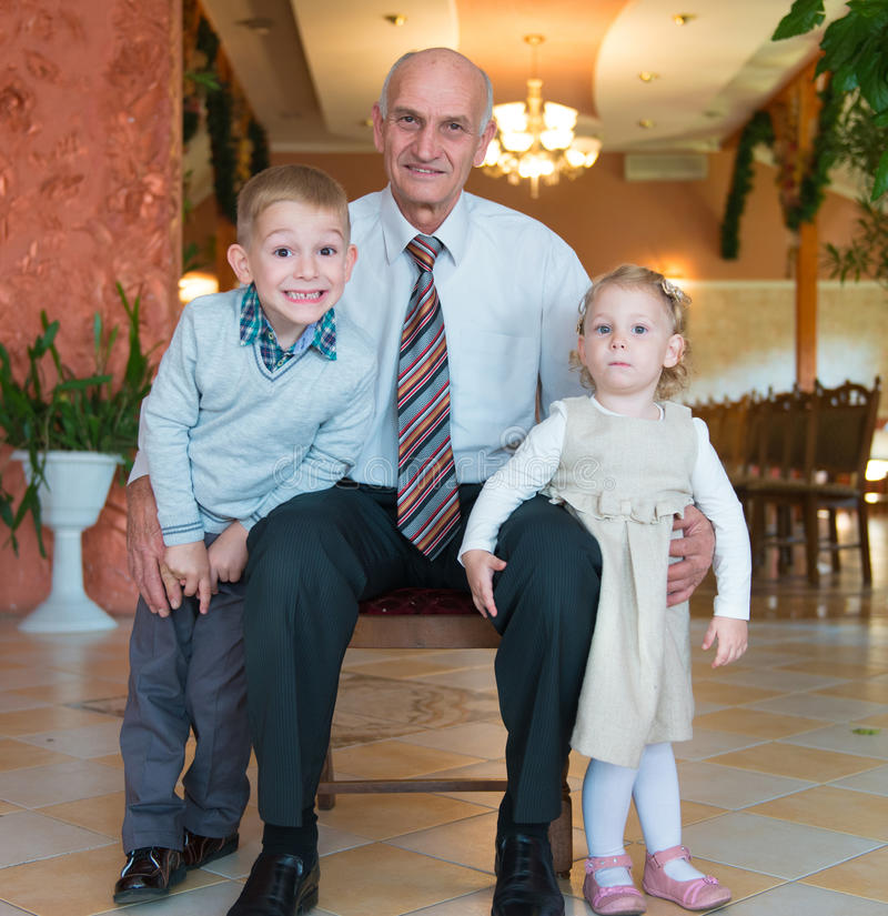 Happy grandfather with grandchildren royalty free stock image