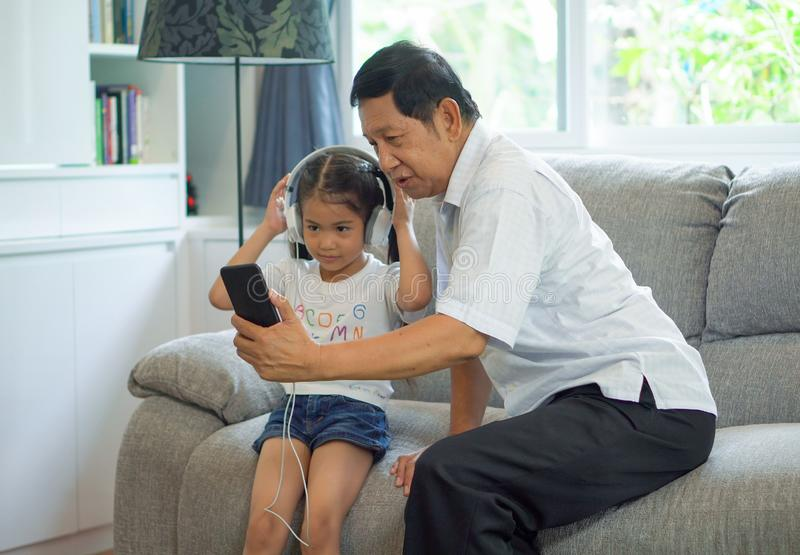 happy Grandfather and granddaughter Sharing smartphone together listening to music with headphone enjoying on sofa in living room stock photos