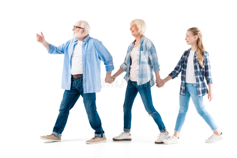 Happy grandfather, grandmother and granddaughter walking and holding hands together royalty free stock photography