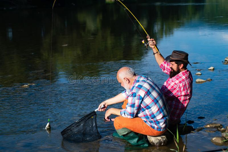 Happy grandfather and grandson with fishing rods on river berth. Men fishing in river during summer day. Father and son. Relaxing together royalty free stock photography