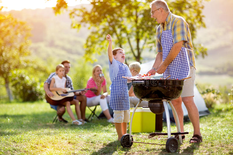 Happy grandfather and grandson making barbecue stock image