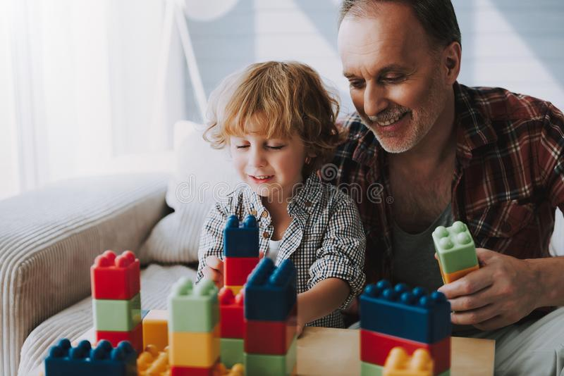 Happy grandfather and little grandson play blocks. Family fun. Leisure with grandson stock photography