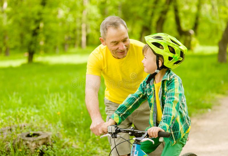 Happy grandfather teaches his grandson to ride a bike stock images