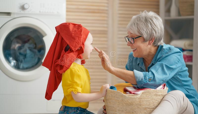 Family doing laundry. Happy grandma and child girl little helper are having fun and smiling while doing laundry at home royalty free stock photo