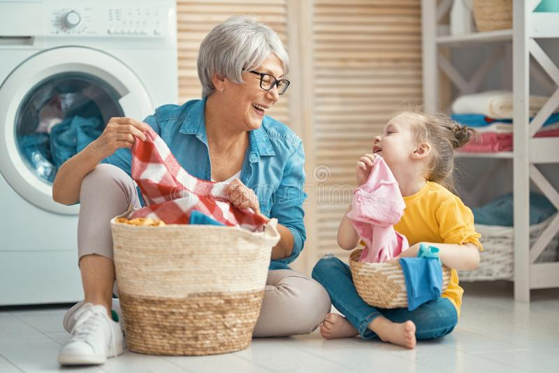 Family doing laundry. Happy grandma and child girl little helper are having fun and smiling while doing laundry at home stock photo