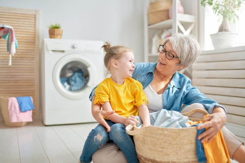 Grandma and child are doing laundry. Happy grandma and child girl little helper are having fun and smiling while doing laundry at home royalty free stock image