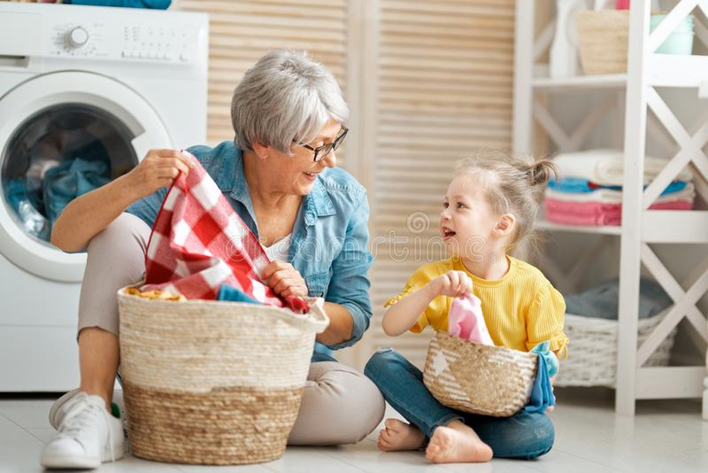 Grandma and child are doing laundry. Happy grandma and child girl little helper are having fun and smiling while doing laundry at home stock image