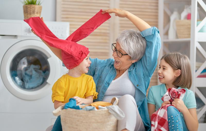 Grandma and children are doing laundry. Happy grandma and children girls little helpers are having fun and smiling while doing laundry at home royalty free stock photography