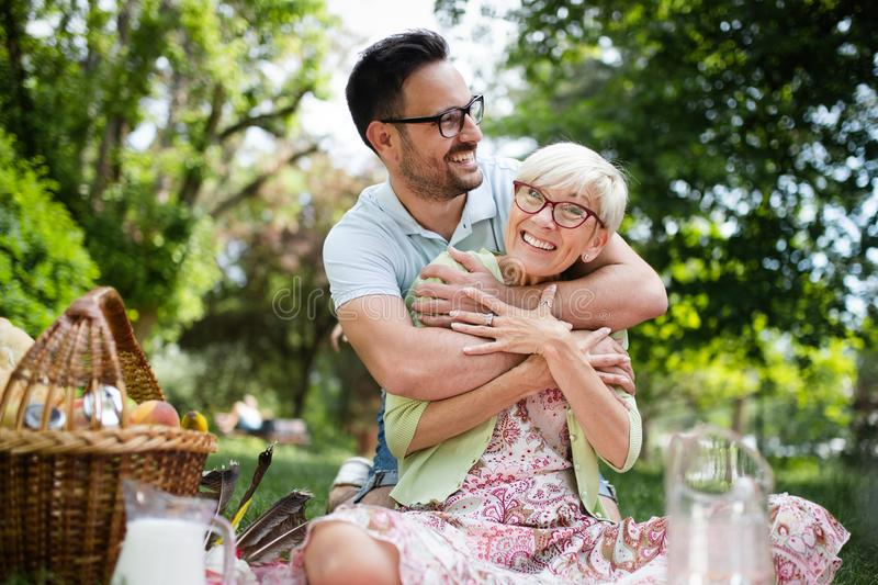 Happy grandma with grandson embracing in a park outdoors stock images