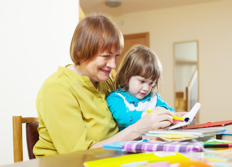 Happy grandmother and child drawing with pencils. Happy grandmother and child drawing with colored pencils together at table stock photo