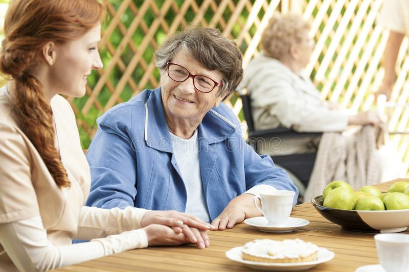 Happy grandmother drinking tea and caregiver royalty free stock images